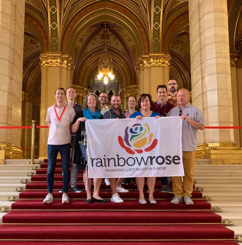 Rainbow Rose a magyar Parlamentben. A csoport zászlóját balról Carola Ebhardt, a német Szociáldemokrata Párt (SPD) és az SPDqueer (az SPD LGBTI csoportja) tagja, jobbról Gurmai Zita, az MSZP frakcióvezető-helyettese és Korózs Lajos, az MSZP országgyűlési képviselője tartja. Fotó: Rainbow Rose Facebook